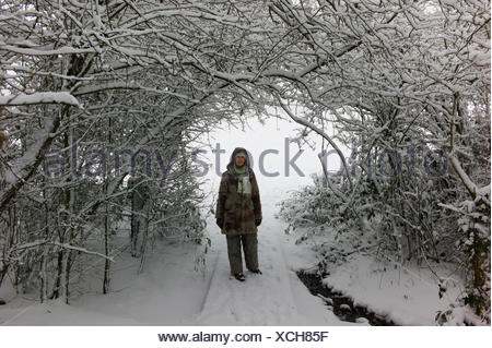 Woman standing in snow, Hampstead Heath, England, UK - Stock Photo