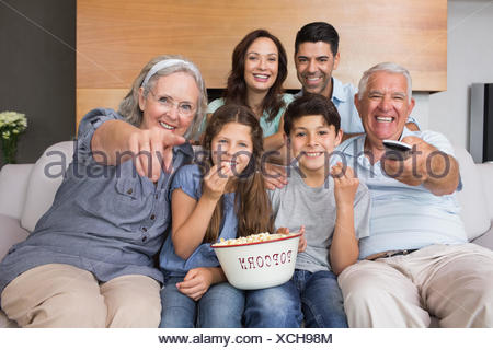 Portrait of happy extended family watching tv in living room - Stock Photo