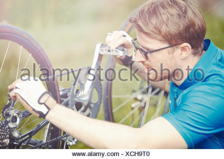 Cyclist mending bicycle chain - Stock Photo