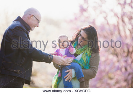 Grandparents and granddaughter in garden - Stock Photo