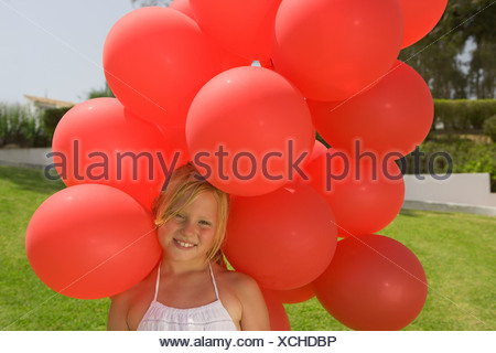 Young girl holding bunch of red balloons - Stock Photo