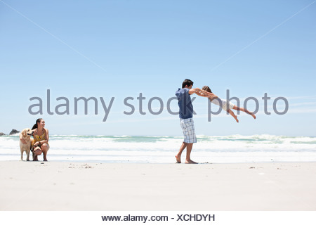 Family with dog walking on beach - Stock Photo