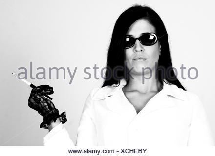 elegante Frau mit Sonnenbrille und Zigarette, Deutschland   woman wearing sunglasses, Germany   BLWS100664.jpg [ (c) blickwinkel - Stock Photo