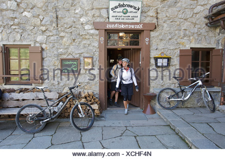 Montainbike riders, female and male, at Karwendelhaus alpine club house, Scharnitz, Tyrol, Austria, Europe - Stock Photo