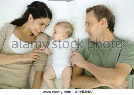 Family resting on bed, baby lying in between parents, overhead view - Stock Photo