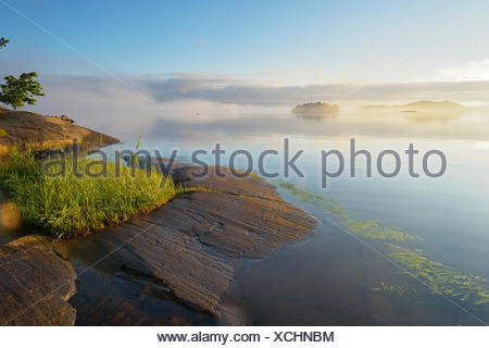 Sweden, Stockholm Archipelago, Uppland, Lidingo, View of lake and islands at dawn - Stock Photo