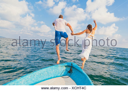 Dressed up man and woman jumping off boat - Stock Photo