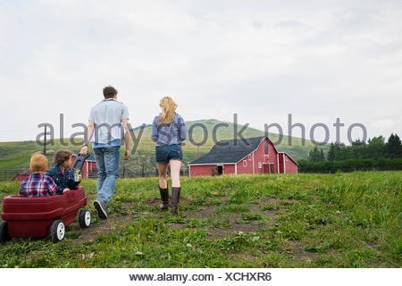 Parents pulling children in wagon outside barn - Stock Photo