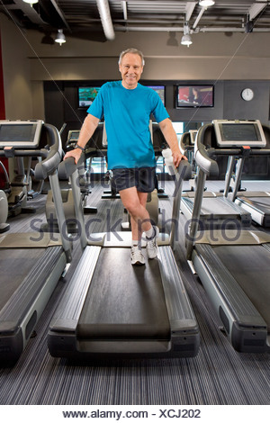 Portrait of smiling man standing on treadmill in health club - Stock Photo