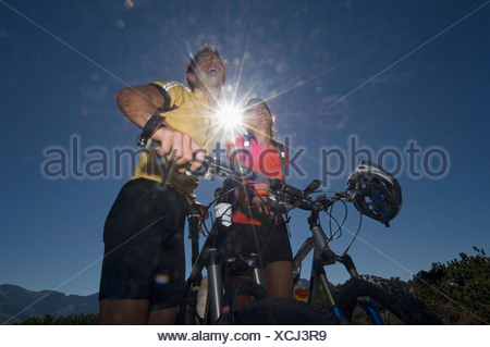 Austria, Salzburger Land, Couple on mountain bikes laughing - Stock Photo