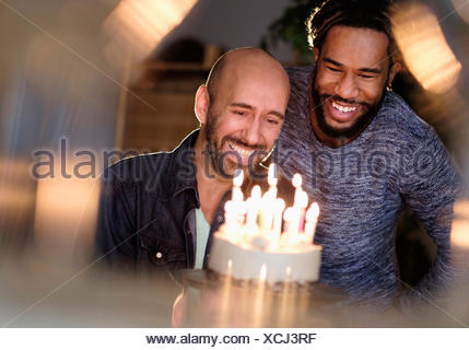 Smiley homosexual couple looking at birthday cake - Stock Photo