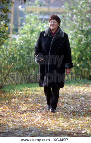 Elderly woman walking routine outside in autumn in park, she looks happy while walking. - Stock Photo
