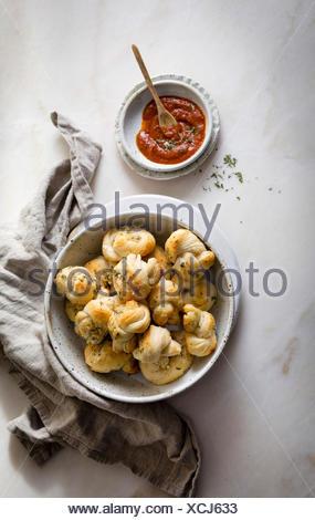 Garlic knots served with marinara sauce - Stock Photo