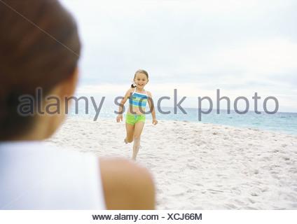 Girl running towards mother on beach - Stock Photo