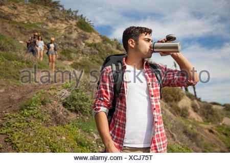 Young man at bottom of hill, drinking from flask, friends trailing behind - Stock Photo