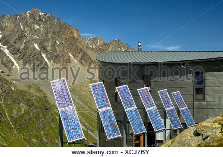 The futuristic Velan Hut, Cabane du Velan, of the Swiss Alpine Club, SAC, with its six solar panels in front of the summit of - Stock Photo