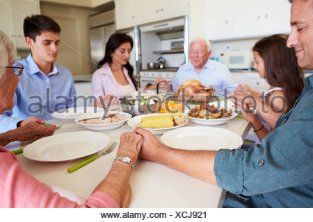 Multi-Generation Family Saying Prayer Before Eating Meal - Stock Photo