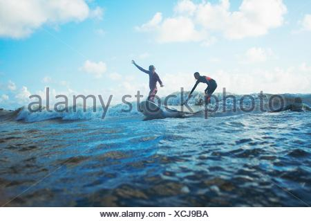 Two surfers surfing in sea - Stock Photo