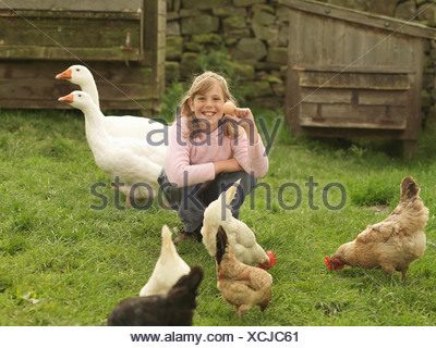Girl Holding Egg With Hens And Geese - Stock Photo