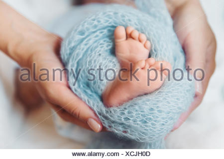 Woman's hands holding her baby's feet in her hands - Stock Photo