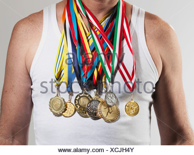 Mature man wearing gold medals against white background - Stock Photo