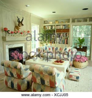 Pale Ikat-style patterned sofas and armchairs beside fireplace in white eighties living room with baskets of pink hydrangeas - Stock Photo
