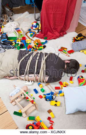 A tied up man in a children's playroom - Stock Photo