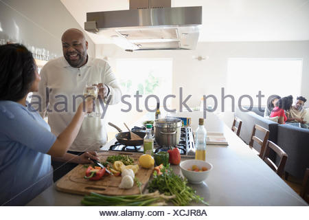 African American couple cooking and drinking white wine in kitchen - Stock Photo