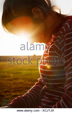 South Africa, Back lit mid adult woman looking down - Stock Photo