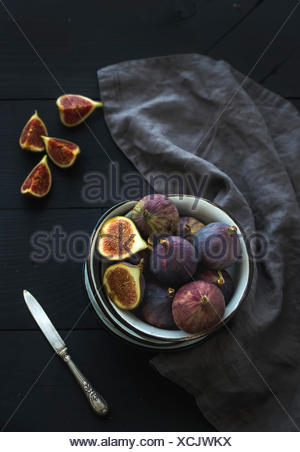 Rustic metal bowl of fresh figs on dark background, top view, selective focus - Stock Photo