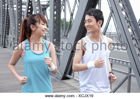 Young man and young woman jogging over bridge - Stock Photo
