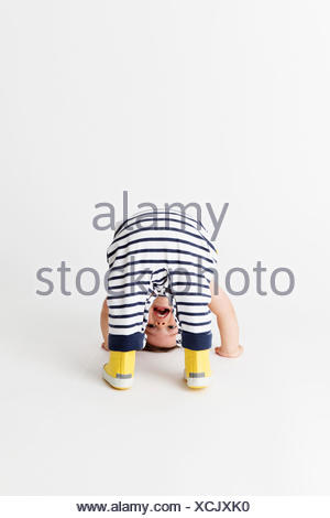 Toddler wearing striped dungarees and yellow rain boots looking through his legs in an upside down position - Stock Photo