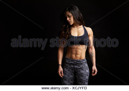 Dark haired woman in sports clothing looking down, portrait - Stock Photo