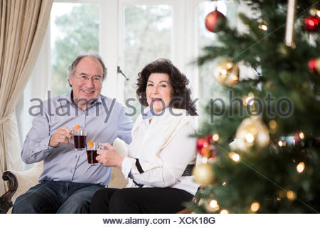 Senior couple drinking punch by Christmas tree - Stock Photo
