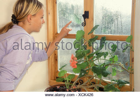 teenage girl looking out of window on rainy day - Stock Photo