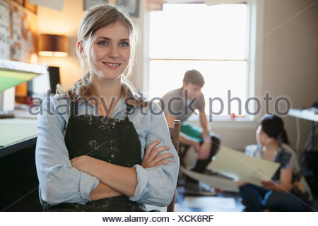 Confident female design professional looking away with colleagues in background at workshop - Stock Photo