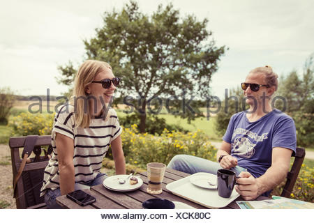 Sweden, Skane, Ostra Goinge, Couple relaxing at table - Stock Photo