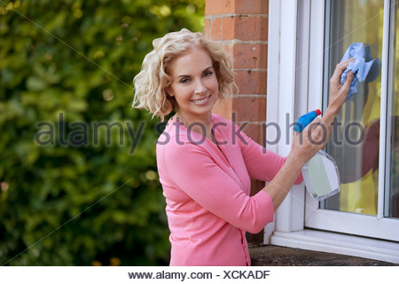 A mature woman cleaning windows of a house - Stock Photo