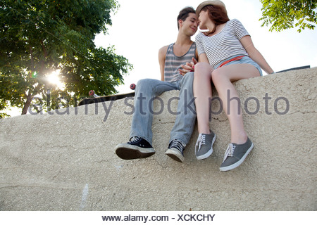 Young couple sitting on wall holding hands - Stock Photo