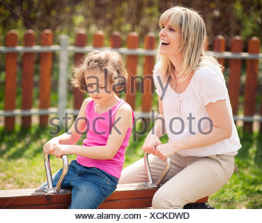Mother and daughter ride seesaw together - Stock Photo