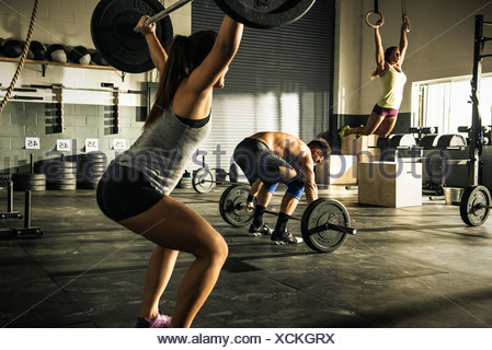 People training with barbells and gymnasium rings - Stock Photo
