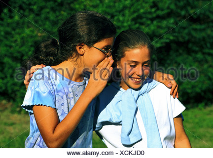 Young girls sharing a secret. - Stock Photo