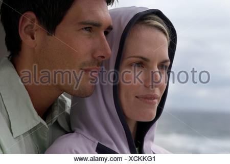 Couple standing on balcony overlooking ocean man embracing woman side view close up - Stock Photo