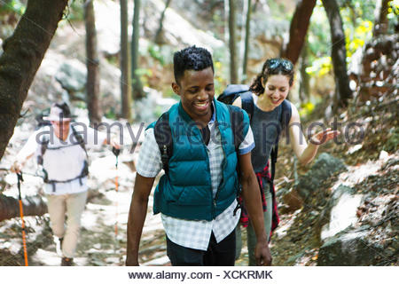 Three young adult hikers hiking up through woodland, Arcadia, California, USA - Stock Photo