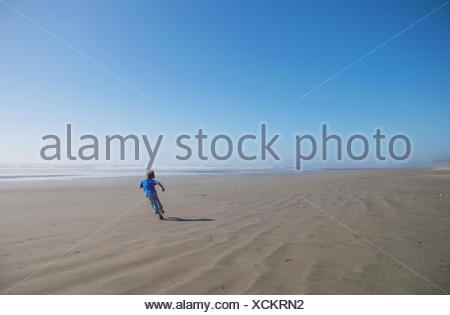 Boy running on beach - Stock Photo