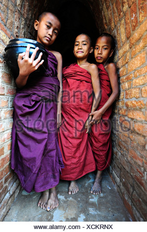 Young Buddhist novices holding alms bowls in front of the old monastery walls at the Shwezigon Pagoda in Bagan, Myanmar, Burma - Stock Photo