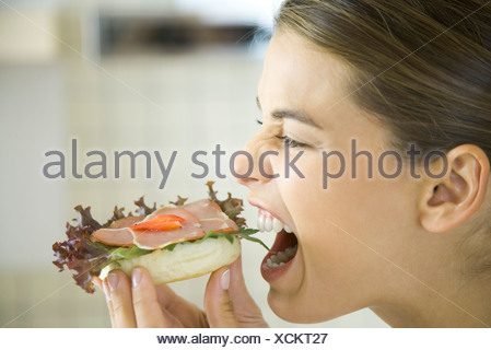 Woman eating open faced ham sandwich, close-up - Stock Photo