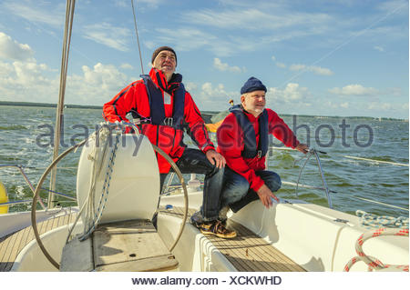 Two men in red jacket standing on the stern of a s - Stock Photo