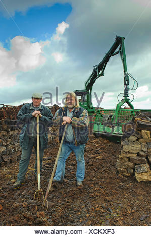 two peat cutters between stacks of bales of peat and the excavator for loading the moor railway, Germany, Lower Saxony, Goldenstedt - Stock Photo
