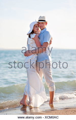 Newlywed couple embracing on beach - Stock Photo